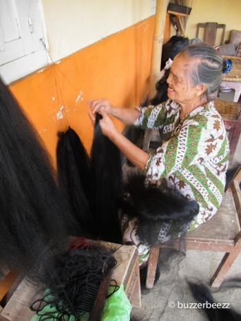 Seorang nenek sibuk menyatukan rambut sintesis helai demi helai